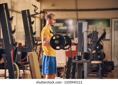 one young man, weight exercise, gym indoors exercise equipemnt, holding heavy weight bar.