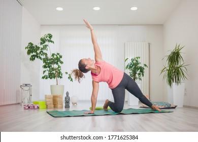 one young middle aged woman practising yoga, indoors in yoga studio, reverse warrior pose (Viparita Virabhadrasana).