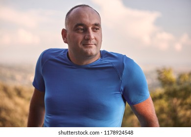 one young overweight man, 30-35 years, looking sideways, upper body shot. outdoors nature.