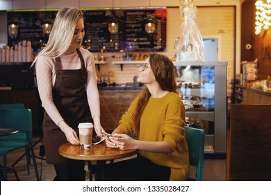 One young pretty woman in glasses with long hair in a mustard sweatshirt sits in a cafe looking at a smartphone. A waitress in a  apron brings food. Style of life, casual, joy of communication, studen