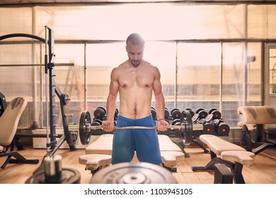 one young shirtless man, looking down, in old beaten up gym indoors, exercise equipment, exercising weight bar.