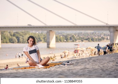 one young smiling girl, posing, looking at camera, sitting in blanket at sandy beach, sunny day. Unrecognizable people behind in background. Summer, casual clothes. Novi Sad, Serbia.