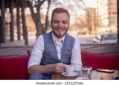 one young smiling man, 20-29 years old sitting in a coffee shop. Espresso cup on table.