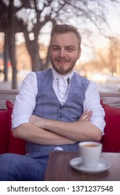 one young smiling man portrait, 20-29 years old sitting in a coffee shop, with arms crossed, looking to camera.