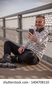 one young smiling man, relaxing, casual clothes wearing inline skates. Taking a selfie, with his phone, on a bridge.