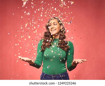 one young smiling woman, 20-29 years, confetti falling down, while her arms are outs outstretched. she is looking friendly and welcoming. shot in studio on pink background.