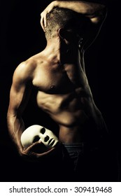 One young undressed faceless man with sexual strong muscular attractive body with raised hand and beautiful chest holding one white mask standing on black studio background, vertical picture