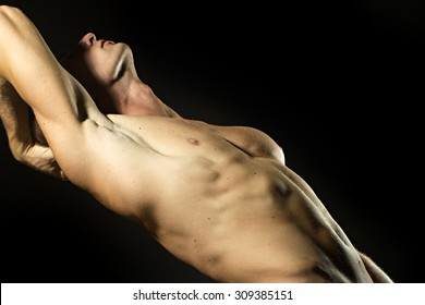 One young undressed man with sexual strong muscular attractive body with raised hand and beautiful chest standing on black studio background, horizontal picture