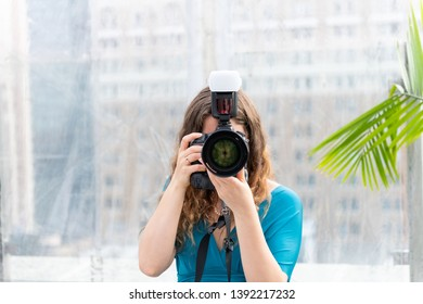 One young wedding photographer woman in dress standing with camera external flash taking picture photo and lens covering face