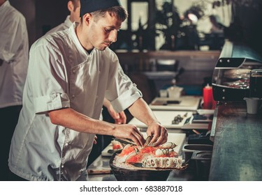 One young white chef dressed in white uniform decorate ready dish in restaurant. He is working on maki rolls. Preparing traditional japanese sushi set in interior of modern professional kitchen