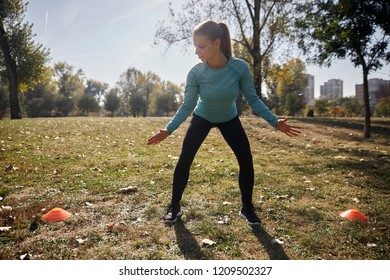 one young woman, 20-29 years old, cardio exercise in public park, between two fitness props,  Lateral Shuffle, outdoors, sunny autumn day.