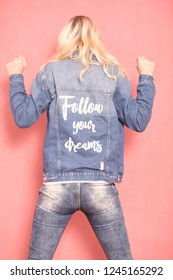 "one young woman, 20-29 years old, long blond hair. Shot in studio on pink background. Wearing jeans jacket with sign ""follow your dreams"" on her back, (rear view)."