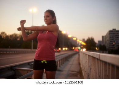 one young woman, 20-29 years, upper body shot, smirking while stretching arms outdoors on a bridge. In background city lights and traffic (out of focus). Warm sunset colors.