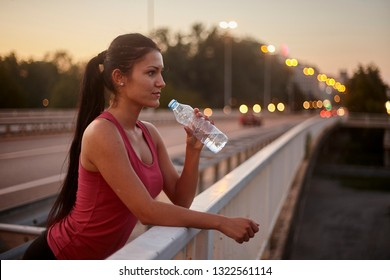 one young woman, 20-29 years, drinking water from bottle outdoors, sport clothing. upper body shot, outdoors on a bridge.