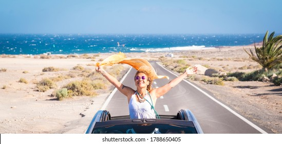 one young woman enjoying and having fun in their vacations outdoors - female person in freedom concept and lifestyle with a car in the middle of the road woth the ocean or sea at the background