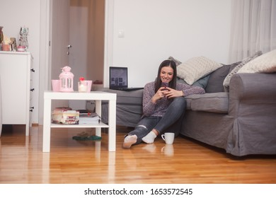 one young woman at her apartment relaxing, typing on her smart phone.
