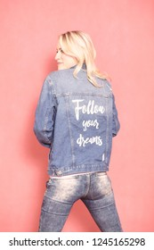 "one young woman, looking sideways, 20-29 years old, long blond hair. Shot in studio on pink background. Wearing jeans jacket with sign ""follow your dreams"" on her back, (rear view)."
