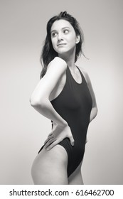 one young woman only, standing swimmer swimsuit, looking sideways glance, black and white