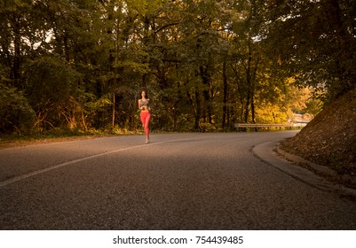 one young woman, outdoors jogging running on asphalt road, forest woods, road asphalt, summer, rural area