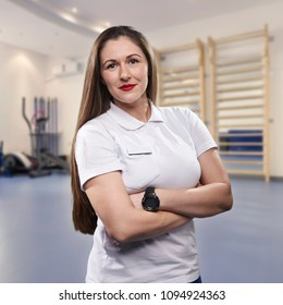 one young woman, physiotherapist portrait, practice room blurred behind.
