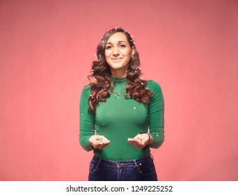 one young woman portrait, 20-29 years, confetti falling down, holding some confetti in her hands, while her arms are outs outstretched. smiling, looking friendly. shot in studio on pink background.