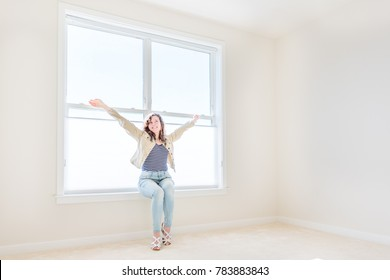 One young woman sitting on windowsill in white, bright empty, clean room on carpet of modern new house, home, apartment looking by sunny large window with blinds, smiling happy