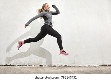 One young woman smiling happy, jumping in mid-air, outdoors, white wall behind, simple minimalistic, sport clothes.