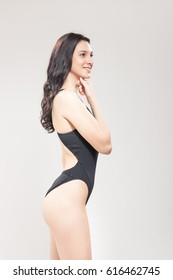 one young woman smiling swimmer swimsuit standing, white background, high key