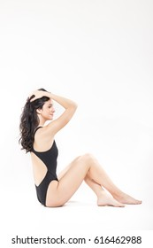 one young woman swimsuit, sitting touching hair, white background