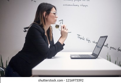 one young woman thinking, 30-39 years old, side view, upper body shot. working on laptop. wall with creative quotes  behind.