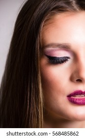 One-half of a sensual woman's face. Beautiful woman closes up. Woman wearing her makeup with her eyes closed.