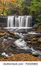Oneida Falls, a beautiful waterfall in Ganoga Glen at Pennsylvania's Ricketts Glen State Park, flows through an autumn landscape.