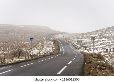One-Lane Winding Road Between Snowy Rolling Field in the Scottish Highlands on a Foggy Winter Day
