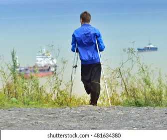one-legged man on crutches standing on the beach looking at ships