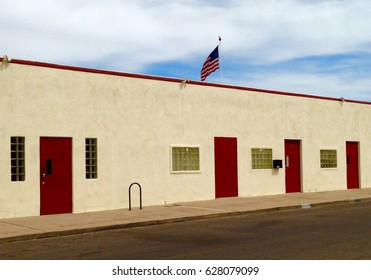 One-level commercial building with red doors and a US flag flying in the background