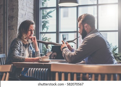 One-on-one meeting. Two young business people sitting at table in cafe.Businesswoman using smartphone. Businessman makes photo on smartphone. On table is laptop and cup of coffee. Couple having dinner.
