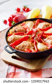 One-pot dish - Chicken thighs and legs baked over a bed of rice and red bell pepper in cast iron stew pan