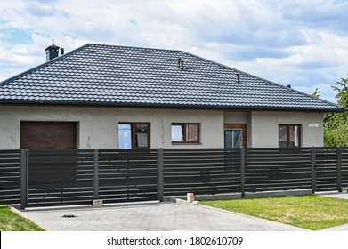 one-story house with gray roof and fence