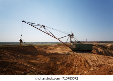 One-tower metal mobile crane on a blue sky background. An industrial moving machine in the sandy quarry. Copy space.