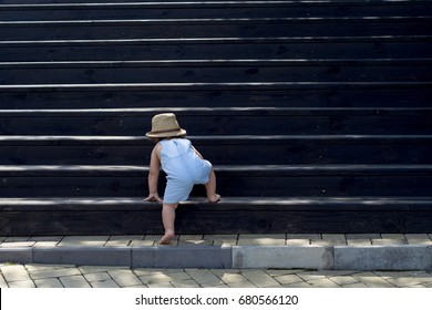 The one-year child climbs up the stairs. Cute baby boy in hat plays on the stairs. The concept of happy childhood. Nature, outdoors, summer