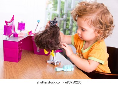 One-year old baby girl playing with dolls, brushing hair, beauty salon