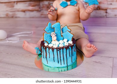 one-year-old baby and a beautiful blue cake with chocolate icing on the child's birthday. first birthday
