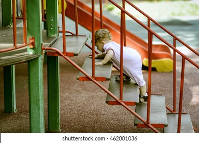 The one-year-old baby climbs up the stairs in summer. Cute baby girl plays on the playground. The independent toddler scrambles up the staircase.