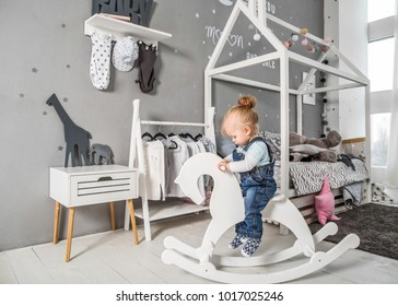 one-year-old girl playing near in the room with a toy horse, skating