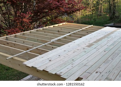 The ongoing construction of an elevated outdoor wooden deck on a late afternoon in Springtime