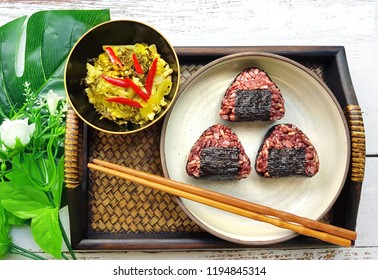 Onigiri , brown rice , with fried preservative vegetable put on bamboo tray decorated with leaves and chopsticks
