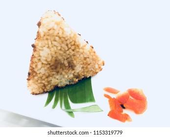 Onigiri, Japanese Food, Kawaii Style Food. Fresh made Japanese onigiri packed in seaweed on a dish. Onigiri rice balls with pickled ginger. Yaki onigiri, grilled rice balls.