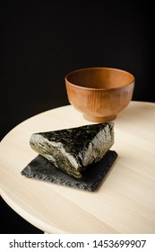 O-nigiri or also known as o-musubi, nigirimeshi, rice ball, is a Japanese food made from white rice formed into triangular or cylindrical shapes and often wrapped in Nori (seaweed), selective focus.