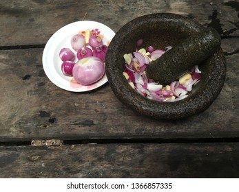 Onion is crushed using a mortar stone. There are groups of onion at the edge of the mortar. Old wooden background.