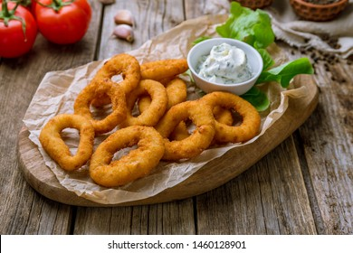 Onion rings in batter on the board on wooden background